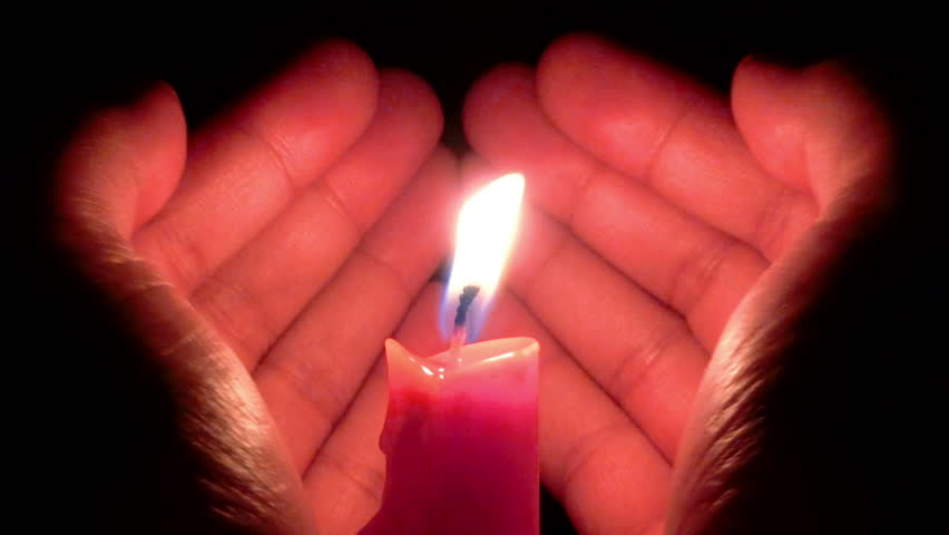 Hands shaped like a heart protect a burning candle in the wind.