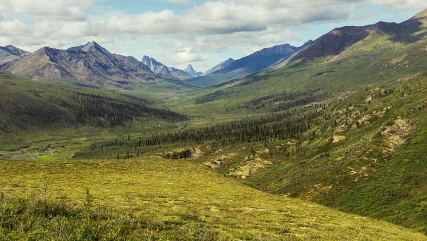 Tombstone Range off the Dempster Highway, Yukon Territory, Canada, one of the great wilderness scenes seen in every direction, on a lucky brighter day with puffy clouds.