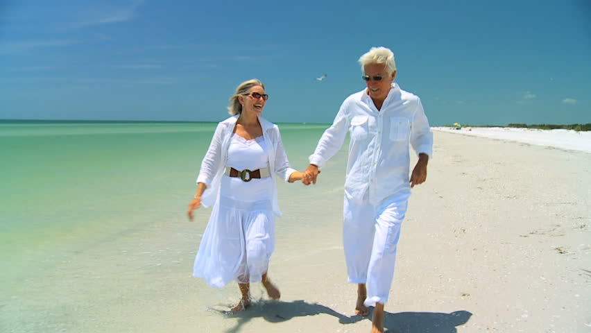 Attractive senior couple dancing on the beach & confidently enjoying a carefree beach lifestyle 60FPS - HD stock video clip