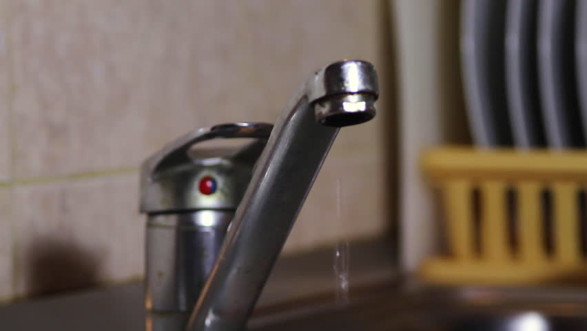 water dripping from a kitchen sink faucet waste