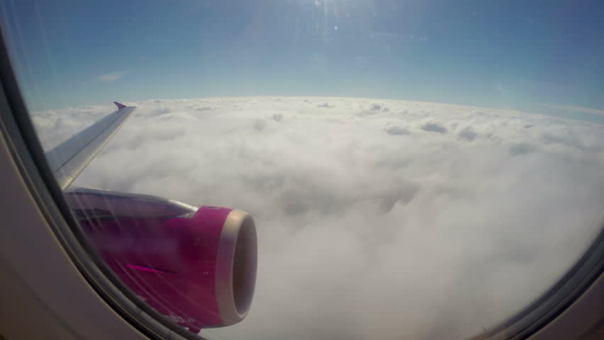 Flying above clouds, airplane wing turbine, passenger porthole