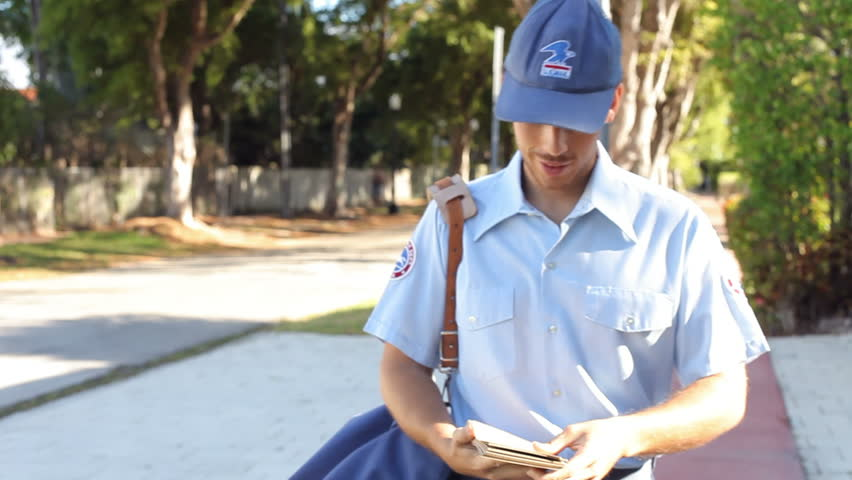 Mailman walks along street carrying letters and looking at houses. Shot on Sony FS700 at frame rate of 25fps