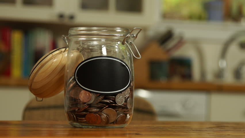 An anonymous person drops some loose change into a saving jar, which has a blank label for your own caption