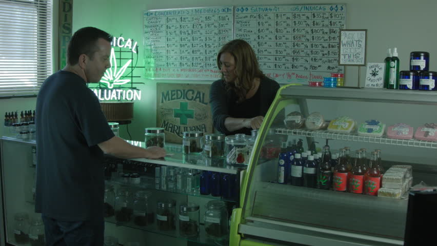 """MEDICAL MARIJUANA DISPENSARY INTERIOR. A FEMALE EMPLOYEE HELPS A MALE CUSTOMER. WIDE SHOT / VERSION 3. ALL LABEL ARTWORK WAS CREATED & CLEARED BY """"PROP HEAVEN"""" IN BURBANK, CALIFORNIA."""