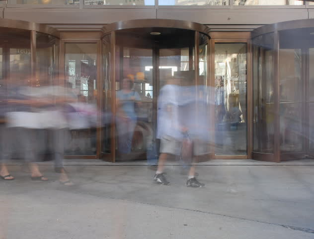 People spinning in and out revolving door time lapse - SD stock video clip