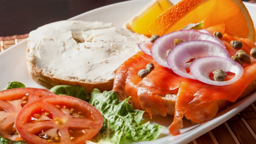 Open face smoked salmon sandwich with cream cheese,chives,onions and a garnish of lettuce,tomato,oranges - 4K stock footage clip