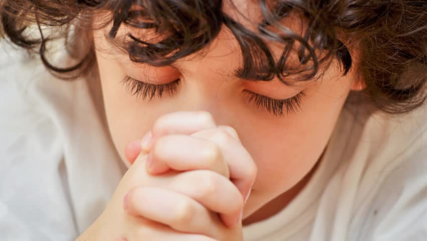Cute Hispanic child with curly hair deep in prayer or earnestly praying to his Creator in heaven. Christian daily devotional of a faithful boy.