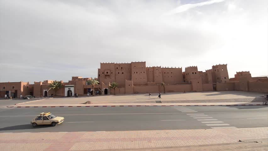 OUARZAZATE, MOROCCO, MARCH 8, 2014. People walking and cars passing by in front of the outer walls of the front façade of Kasbah Taourirt in Ouarzazate, in Morocco, on March 8th, 2014.