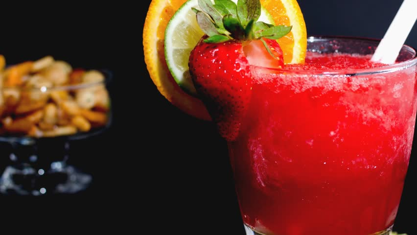 Delicious and refreshing strawberry daiquiri garnished with lime and orange. International and popular alcoholic drink.