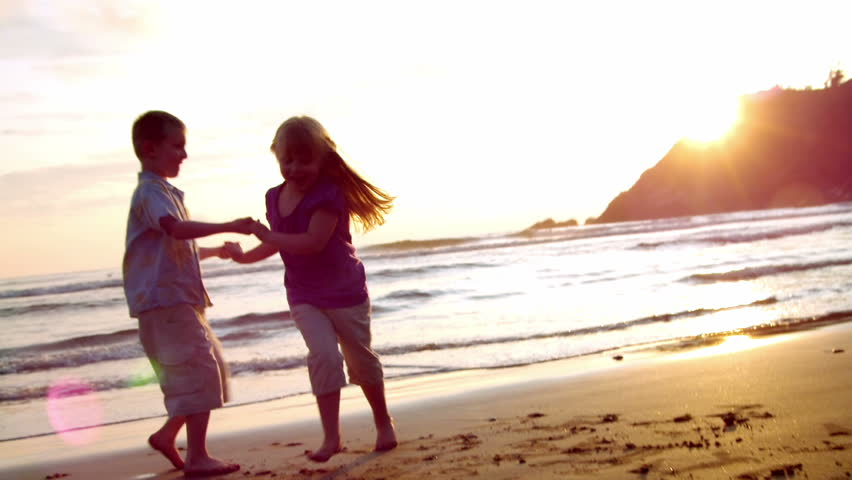 two children dance on the beach at sunset. lens flare.  - HD stock footage clip