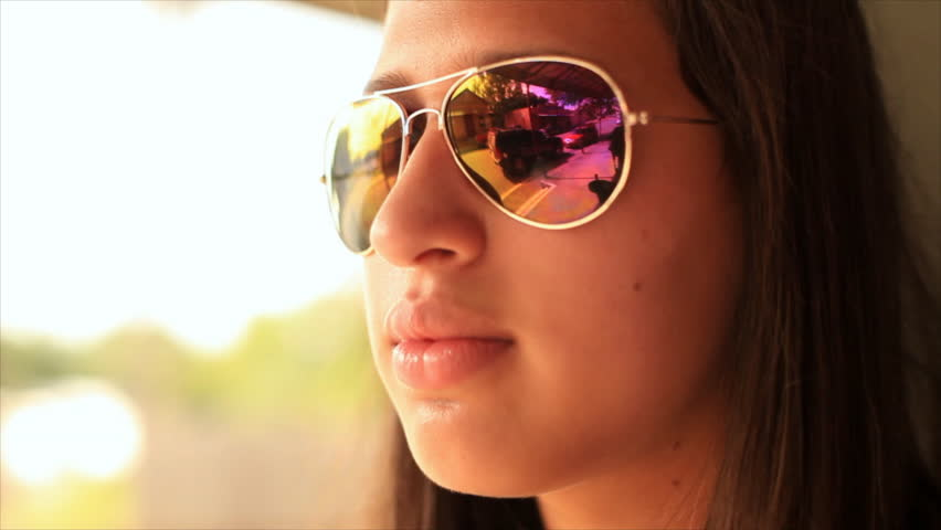 A girl in large reflective sunglasses leaning up against a colorfully painted wall. - HD stock footage clip
