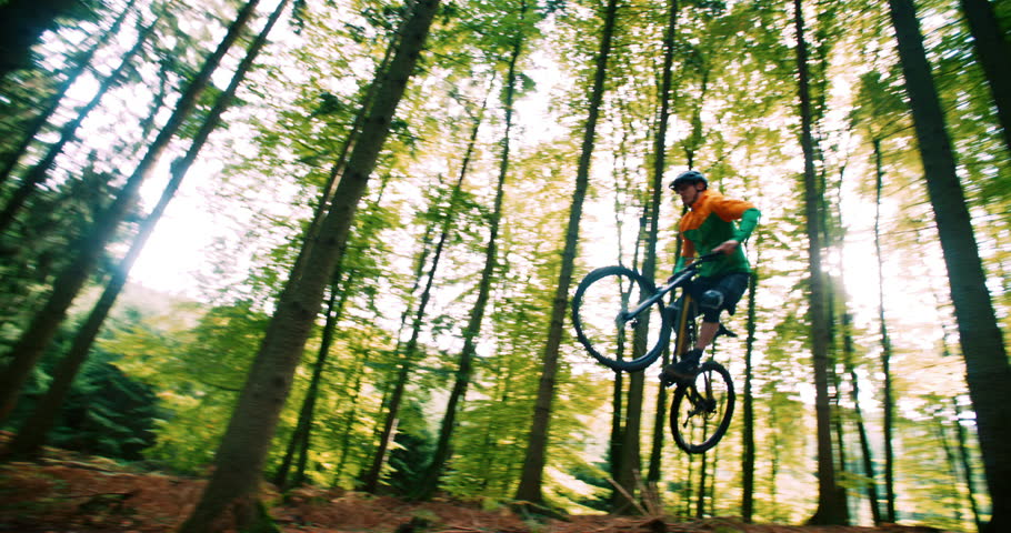 Man on mountain bike jumps high in 4k slow motion in forest