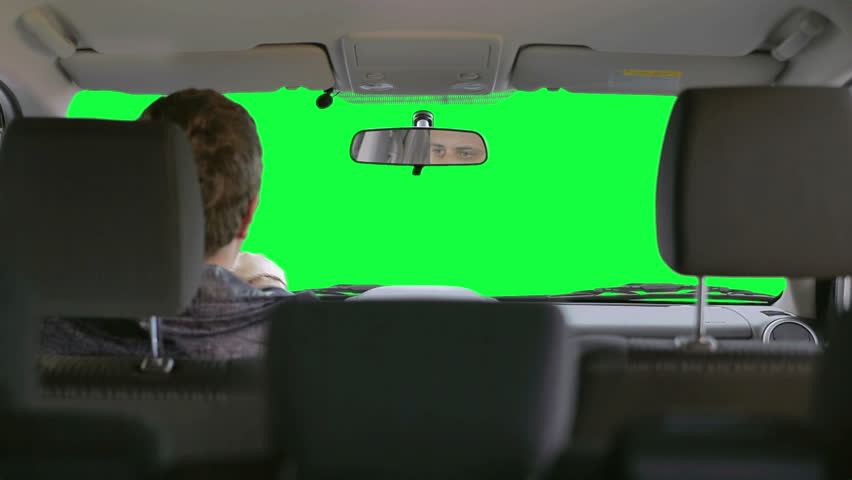 The driver looking in the rear-view mirror. View from the the back of passenger compartment