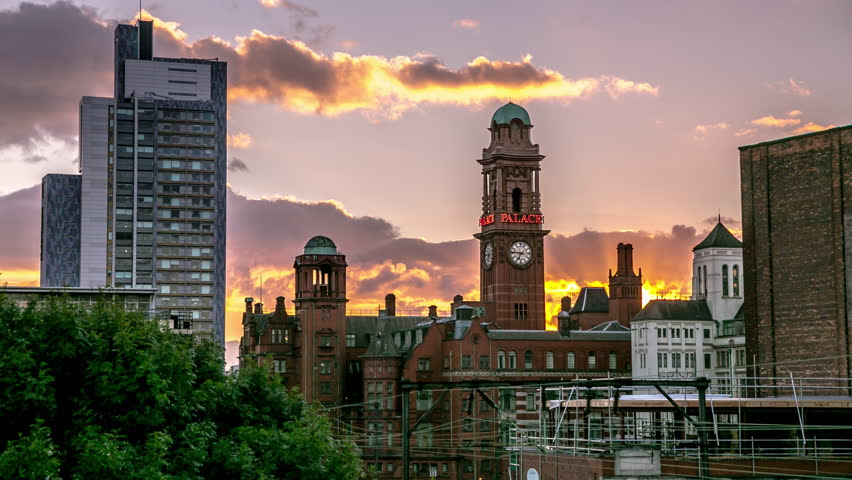 Time lapse of the Manchester skyline as the sun sets, camera slides down behind fence