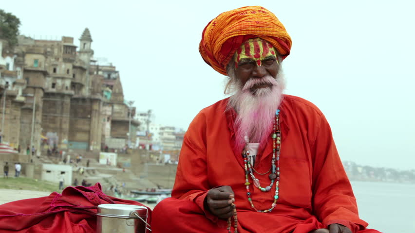 Sadhu at the ghats in Varanasi, India. With a pink beard from the traditional holi festival. - HD stock footage clip