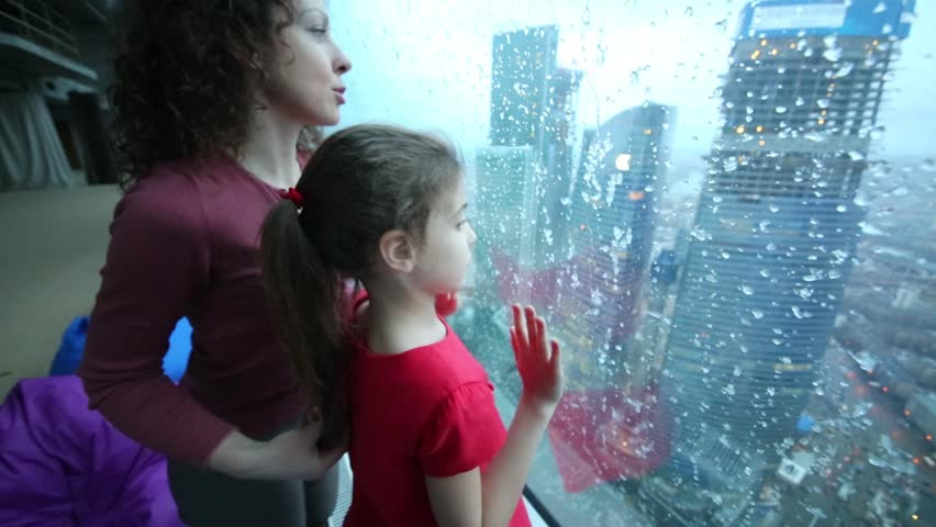 Mother and daughter look through large window with frozen drops on modern city - HD stock video clip
