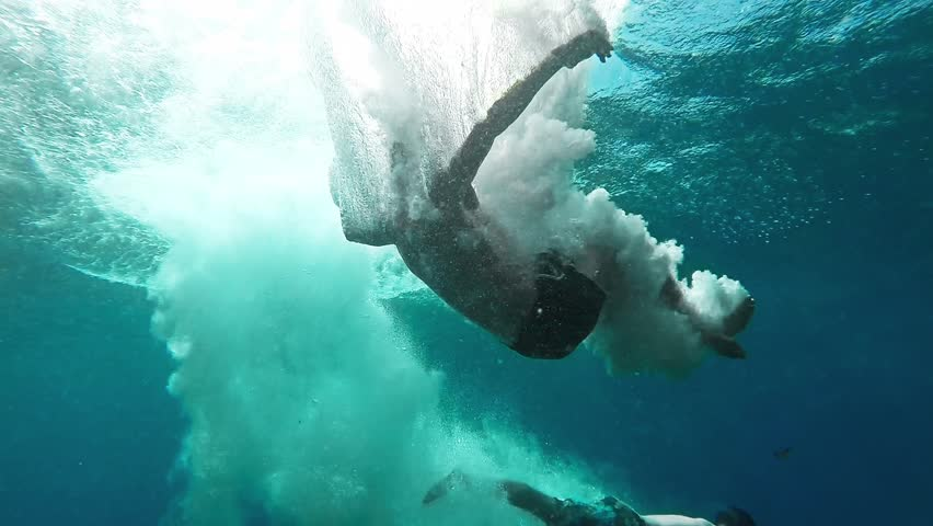 Two Young Men Jumping Into Deep Blue Sea Water Ocean