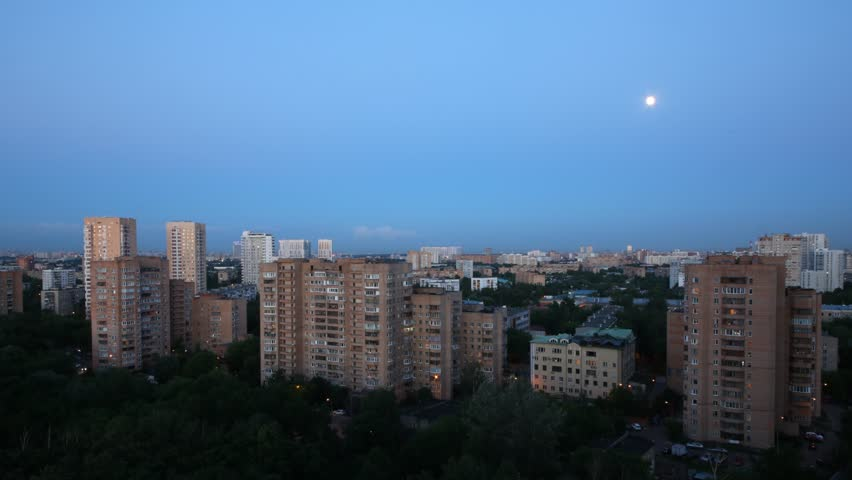 Evening on the town, the moon moves across the sky. Time lapse. - HD stock video clip
