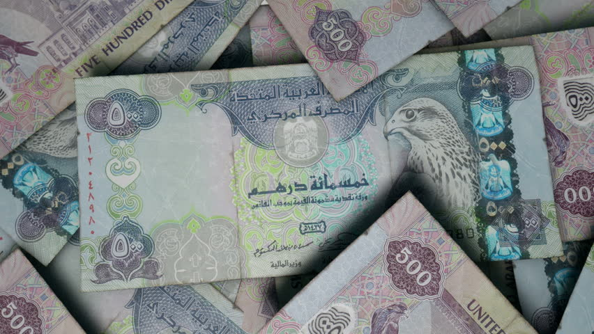 An extreme close up pan of a pile of randomly scattered dirham banknotes