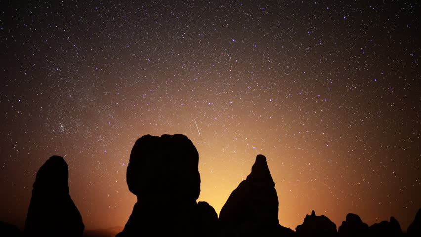 4K Astrophotography time lapse footage with pan right motion of star trails over monolithic formations in Trona Pinnacles, California