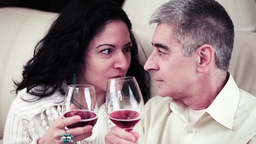 Video of a happy mature couple talking closely and toasting with glasses of red wine.