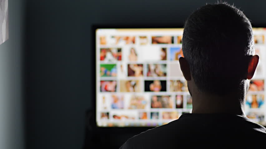 man watches surfing pornography site looking for virtual sex at night in a dark room,screen is out of focus uhd 4k,useful to represent internet easy porn accessibility and social issue