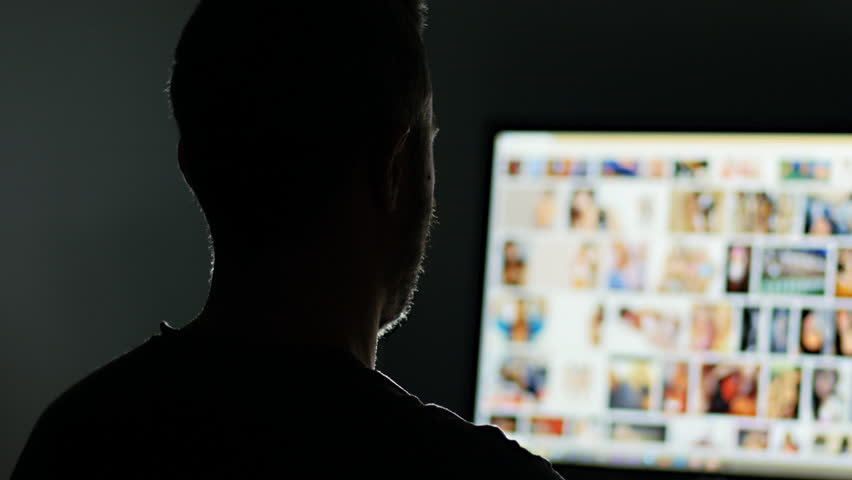 man surfing watching pornography site on the web looking for virtual sex at night in a dark room,screen is out of focus uhd 4k,useful to represent internet easy porn accessibility and social issue