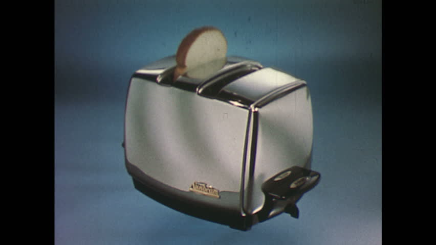 1960s Toaster With Bread ~ United states s hand puts bread in toaster interior