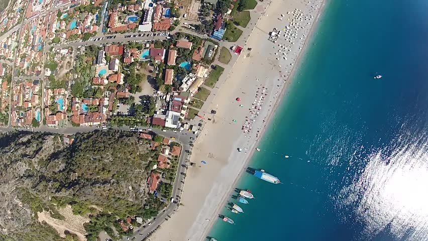 Base jumper flying above coastline with spectacular views of surrounding landscape.  Sky diving and parachuting daredevils B.A.S.E jump from great heights.