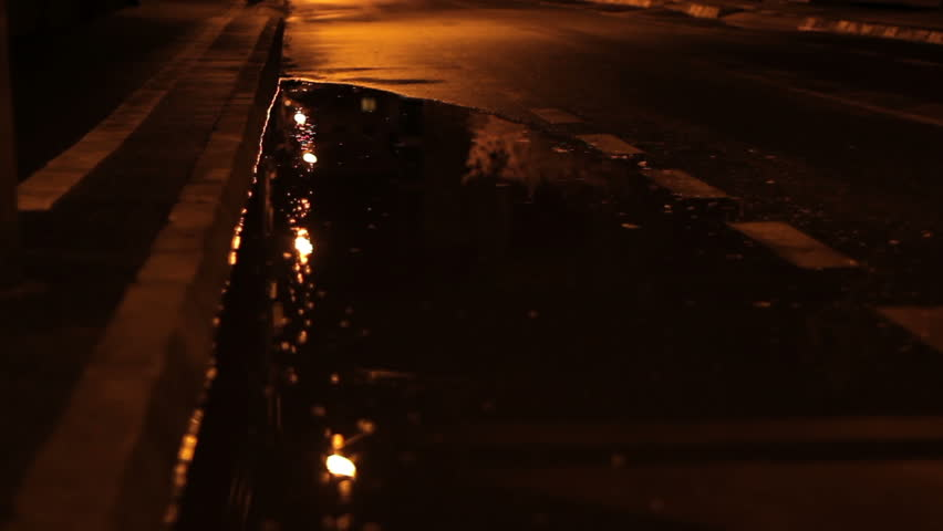 On a dark empty alley with puddles after an autumn rain, in a cold night an unidentified man runs and walks hurried.