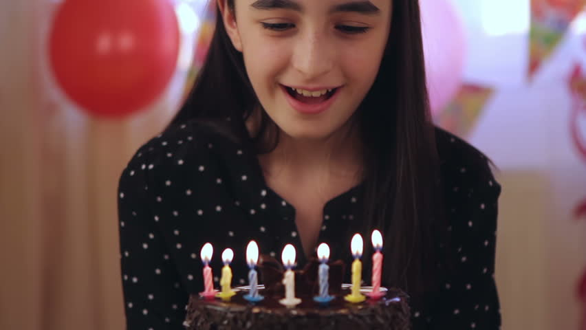 Happy young girl blowing out candles on a birthday cake.