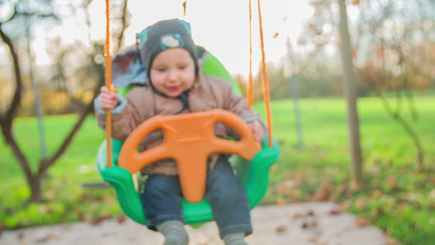 smiling blue eyes baby boy on a backyard swing slow motion close up