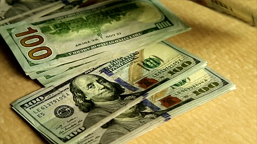 Close-up of US Dollars bills. Stack of $100 dollars.  Shot with HD camera and  real money is used. No animation, effects or graphics. - HD stock footage clip