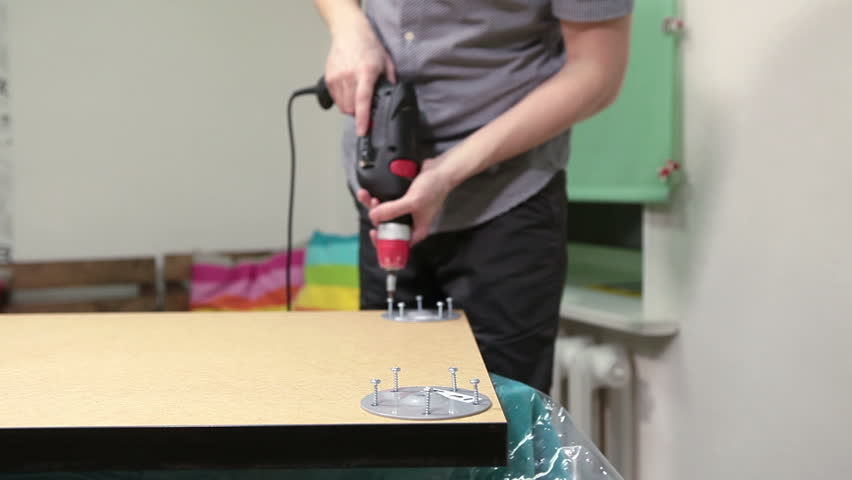 Worker holding electric drill in hands while installing table legs at home, foreground focus
