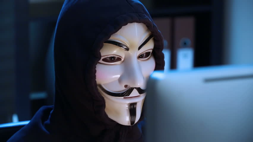 MOSCOW, RUSSIA - FEBRUARY 25, 2015:  The hacker in a mask of Guy Fawkes uses the computer late at night. Close up. Dolly shot.