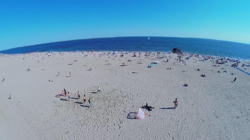 NEW-YORK - AUG 24, 2014: People play football and get rest on Brighton Beach at summer sunny day. Aerial view. Brighton Beach is an oceanside neighborhood with a total of 31,228 households. - HD stock footage clip