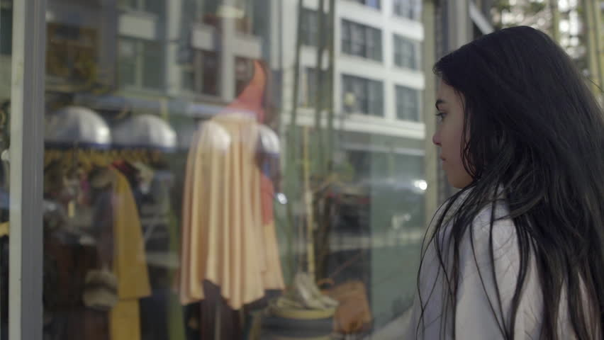 Mixed Race Young Woman Stops To Look At Window Display In City, Then Continues Walking