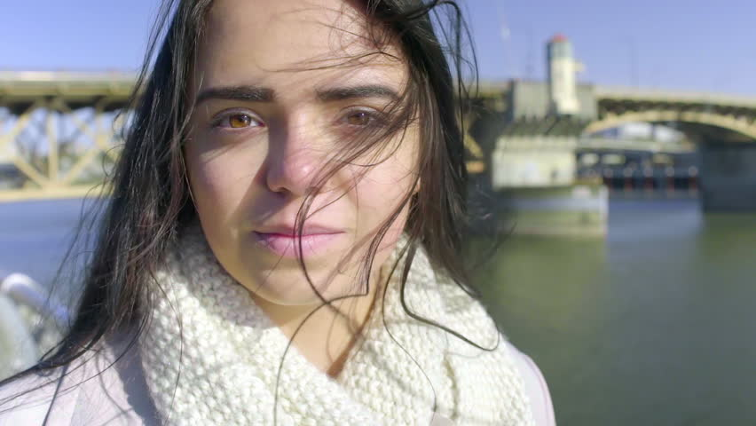 Carefree Mixed Race Young Woman Smiles, Her Hair Blows In The Wind, River In Background