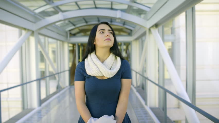 Mixed Race Young Woman Walks Through A Skybridge, She Looks Around In Awe