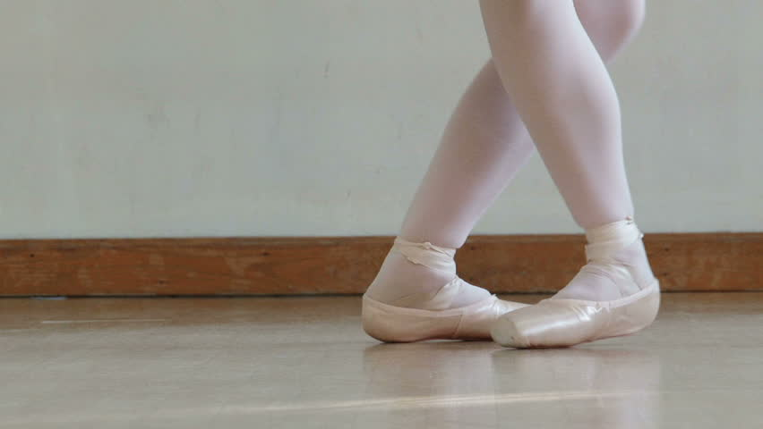 Close up of a ballet dancer's feet as she practices point exercises.