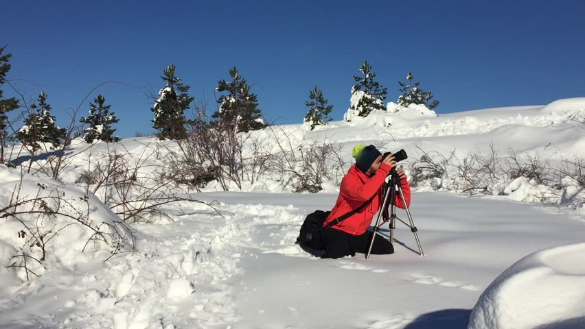 Man with camera and tripod taking photo outdoors in winter snowy landscape. - HD stock video clip
