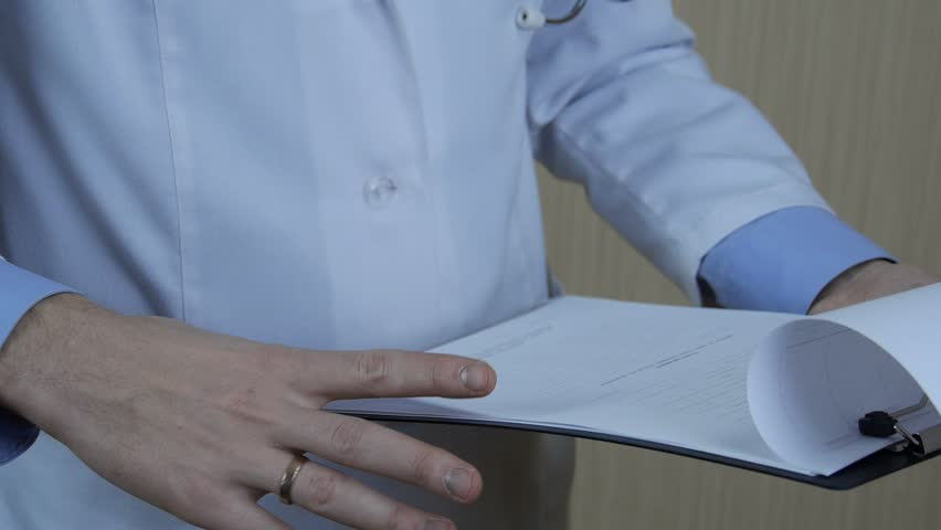 Doctor examine, review forms with the testimony of evaluable patients. The patient is healthy, the doctor carefully examines evidence analysis.