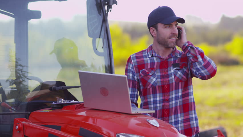 Farmer using laptop computer and cell phone