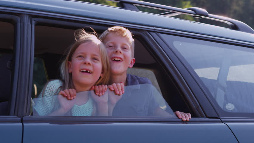 Two children looking out car window