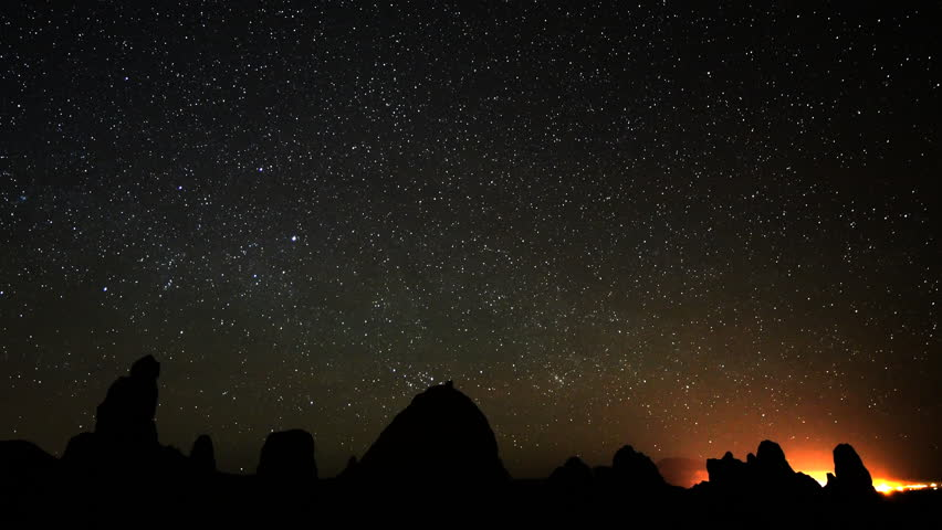 4K Astrophotography time lapse footage of starry sky over tufa formations at dawn in Trona Pinnacles, California, long shot