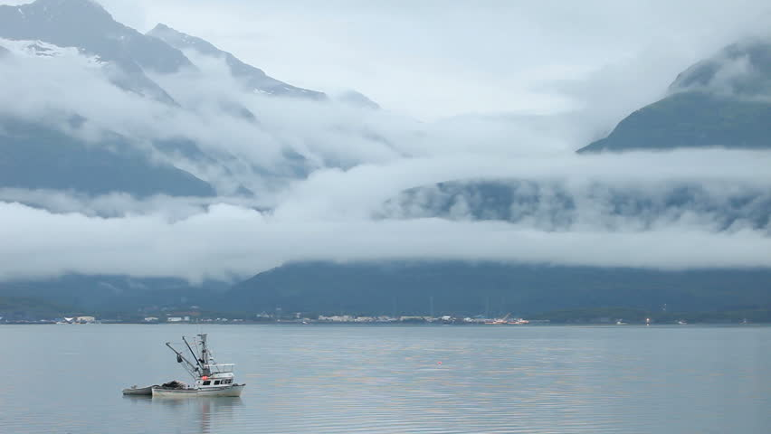 Fishing trawler anchored in fjord bay with Valdez, Alaska, mountains and beautiful fog and clouds in the background. Early morning calm. - HD stock video clip