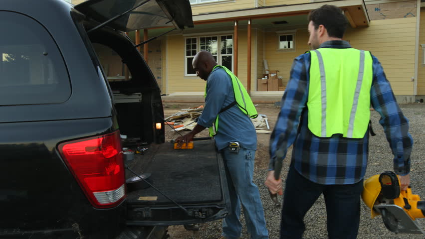 Construction workers get tools from truck