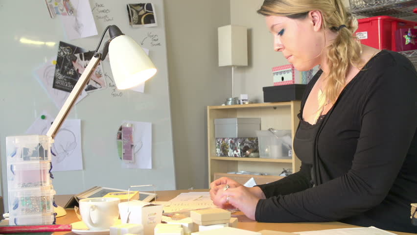 Woman running jewelry business from home puts customer order in envelope and attaches label.Shot on Sony FS700 at frame rate of 25fps