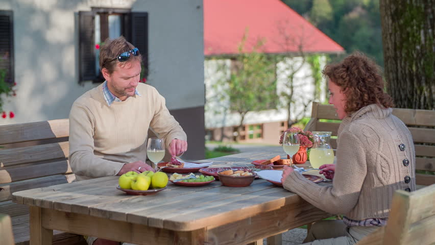 In the middle of meal woman feeds man with a cheese. Couple seating at the table on the garden f the restaurant and the woman feeds the man with cheese in the beautiful scenery on the sunny day.