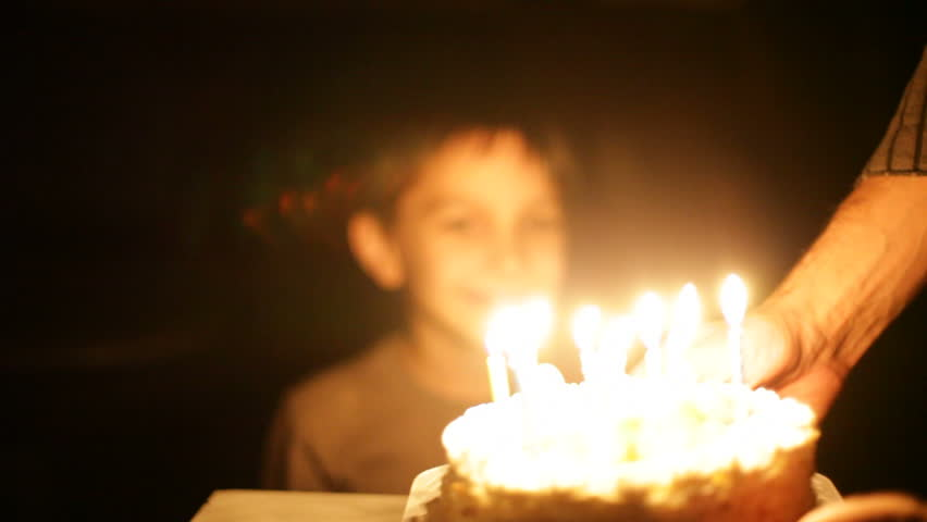 boy blows out candles on birthday cake.  - HD stock footage clip